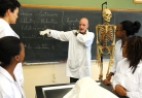Lecturer and students around skeleton in anatomy class